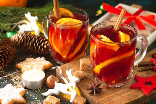 冬のクリスマスは、お祝いのテーブルにオレンジとスパイスを使ったグリューワインのクローズアップです。