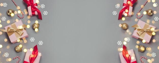 Зимний рождественский или новогодний баннер с бумажными розовыми подарками и рен лентами, леденцами, конфетти и серебряными шариками на сером фоне.