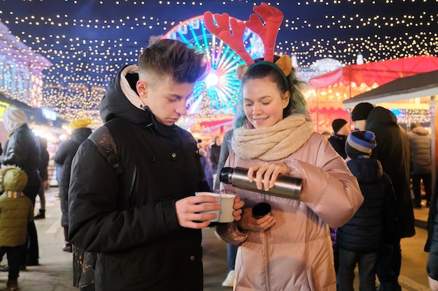 Winter christmas portrait of happy teenagers boy and girl at holiday market