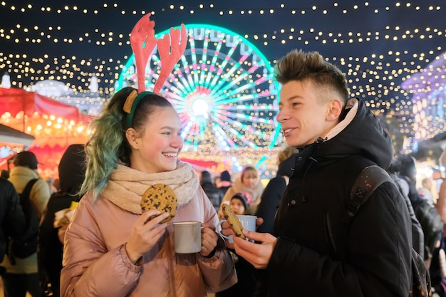Winter christmas portrait of a happy teenagers boy and girl at holiday market