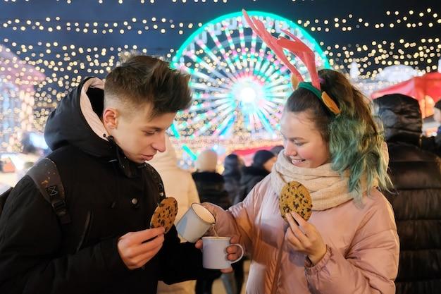Зимний рождественский портрет счастливых подростков, мальчика и девочки на праздничном рынке