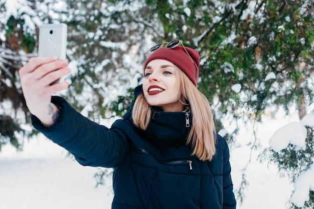 겨울, 크리스마스, 기술, 사람, 라이프 스타일 및 뷰티 개념 -셀피 시간. 그녀의 스마트 폰으로 셀카를 하 고 예쁜 갈색 머리 소녀. 아름 다운 젊은 여자. 야외 겨울 초상화입니다.