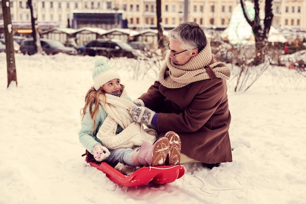 Winter city. handsome gray-haired man sitting in semi position and talking to his kid