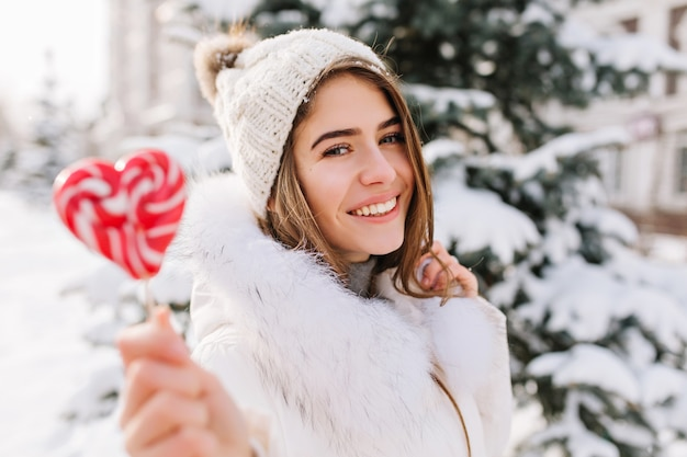 Winter closeup portrait charming joyful young woman in sunny winter morning with pink lollypop on street