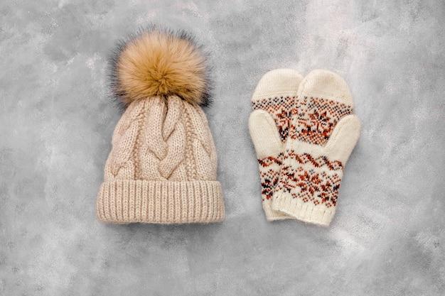 Зимняя одежда варежки и вязаные хатоны на сером каменном фоне