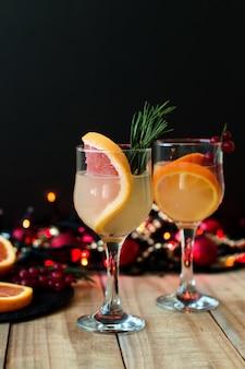 Зимний коктейль с грейпфрутом, розмарином, апельсином и красной смородиной в фужерах.