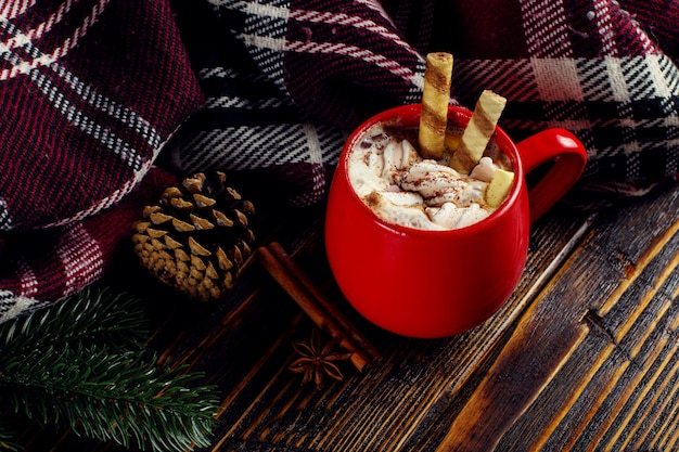 Winter coffee drink, cocoa with whipped cream and marshmallows in a red ceramic cup