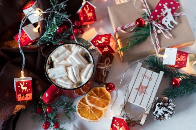 Зимний кофе с зефиром в красной чашке и новогоднее украшение