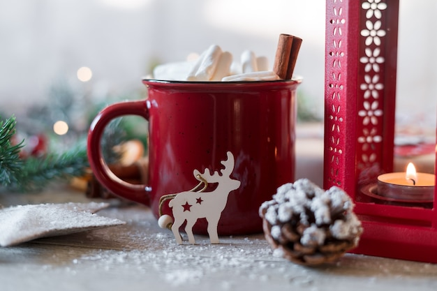 Winter coffee with marshmallows in red cup and christmas decoration
