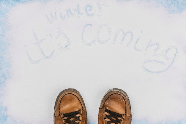 Winter coming writing with brown shoes down