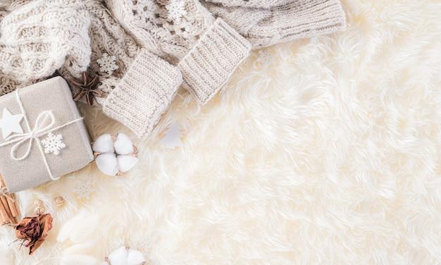 Зимняя композиция. подарочная коробка кофейная чашка, палочки корицы, звездочки аниса, бежевый свитер с вязанным пледом на кремовом сером пушистом фоне. плоский вид сверху копией пространства.