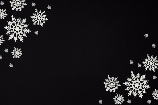 Winter composition made of snowflakes on black background with copy space, christmas card, flat lay, top view