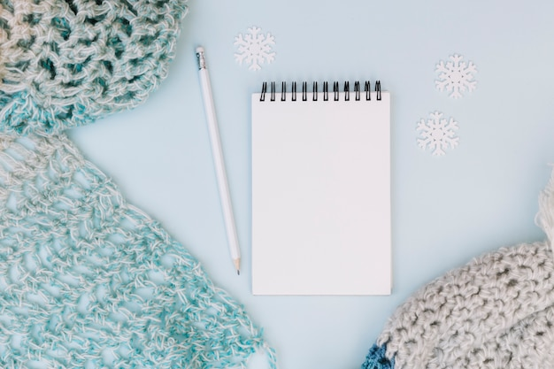 Winter composition of notepad with scarf