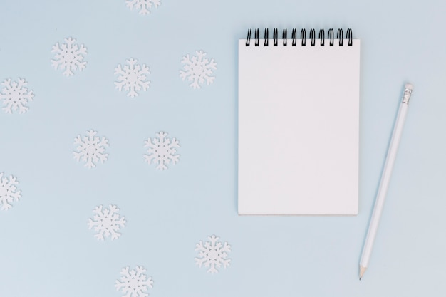 Winter composition of notepad with snowflakes