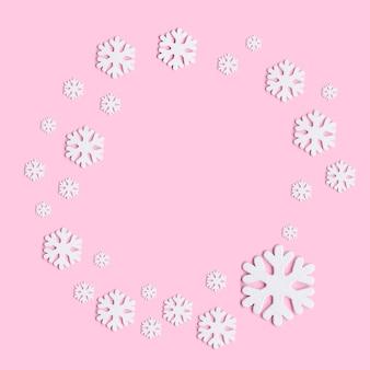 Зимняя композиция из снежинок на пастельных розовом фоне.