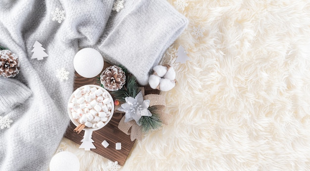 크림 컬러 니트 담요와 푹신한 배경에 겨울 구성.