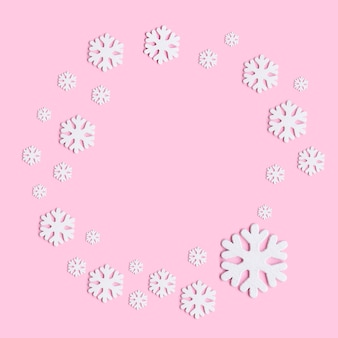 Winter composition of snowflakes on pastel pink background.