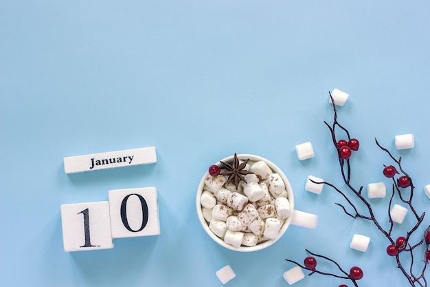 Winter composition. white wooden calendar cubes. data january 10. cup of cocoa, marshmallows and decorative branch