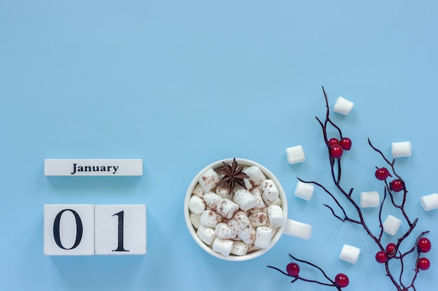 Winter composition. white wooden calendar cubes. data january 1st. cup of cocoa with marshmallows and decorative branch