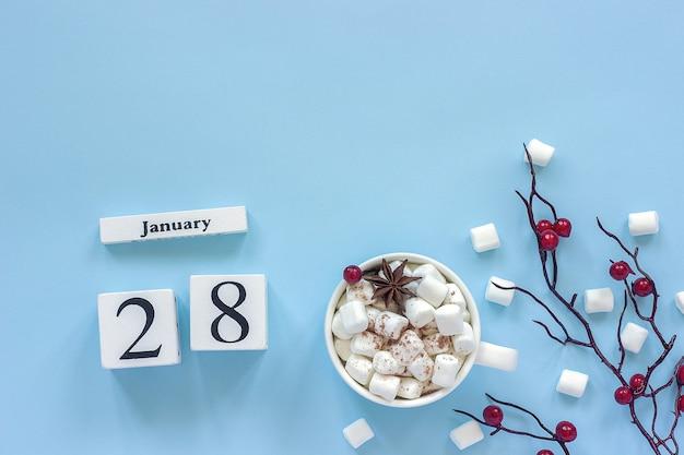 Зимняя композиция. белые деревянные кубики календаря. данные 28 января. чашка какао, зефир и декоративная ветка с красными ягодами на синем фоне вид сверху плоская планировка копирование пространства
