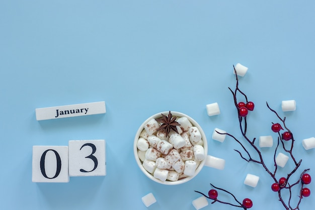 Winter composition. white wooden calendar cubes. data january 3. cup of cocoa, marshmallows