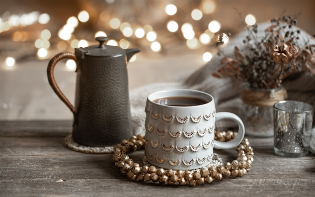 Зимняя композиция с красивой чашкой горячего напитка и чайником