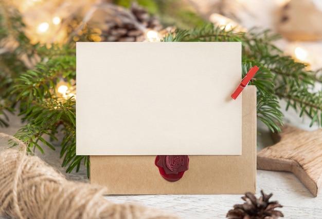 Зимняя композиция с пустой картой, запечатанным конвертом и еловыми ветками заделывают. рождество и новый год шаблон поздравительной открытки с фоном огней. праздничный макет.