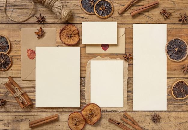 Зимняя композиция с пустой карточкой, запечатанным конвертом, специями и сухофруктами на деревянном столе