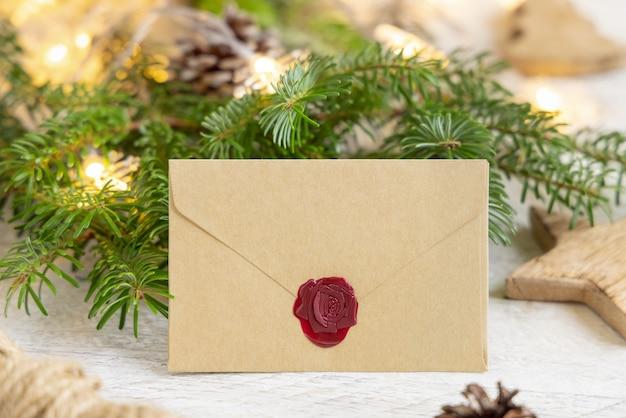 Зимняя композиция с запечатанным конвертом и еловыми ветками заделывают. рождество и новый год шаблон поздравительной открытки с фоном огней. праздничный макет.