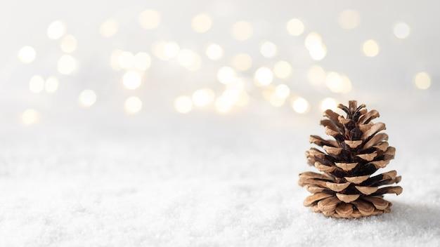 Зимняя композиция с шишкой на фоне размытых рождественских огней