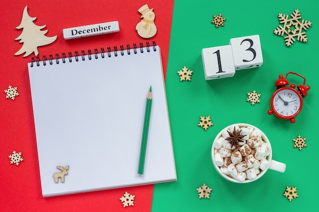Winter composition. wooden calendar december 13th cup of cocoa with marshmallow, empty open notepad with pencil