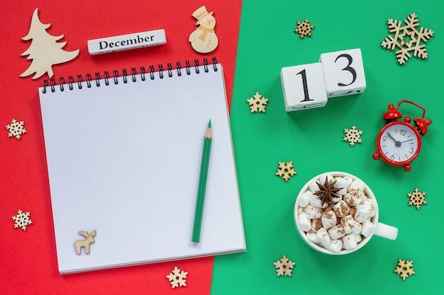 冬の組成物。木製カレンダー12月13日マシュマロとココアのカップ、鉛筆で空のメモ帳を開く