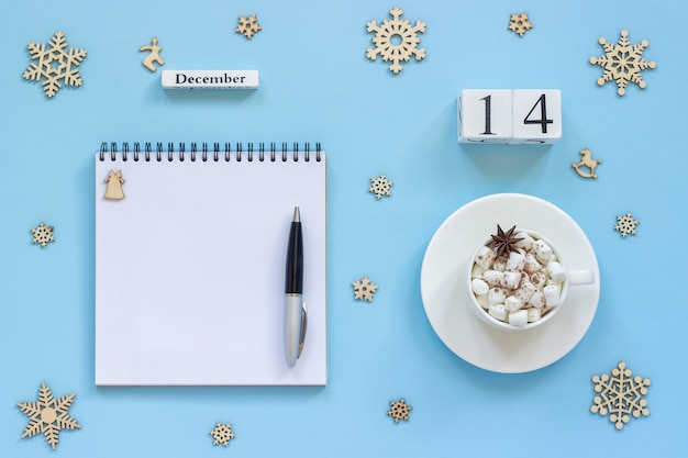 Winter composition. wooden calendar december 14 cup of cocoa with marshmallow and star anise, empty open notepad with pen and snowflake on blue background. top view flat lay mockup concept
