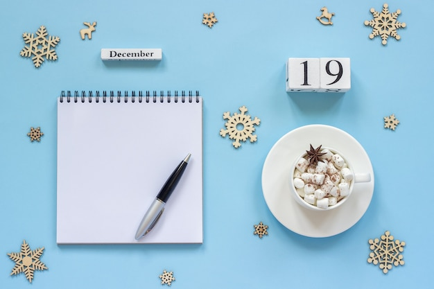 Winter composition. wooden calendar december 19 cup of cocoa with marshmallow and star anise, empty open notepad at lay mockup concept
