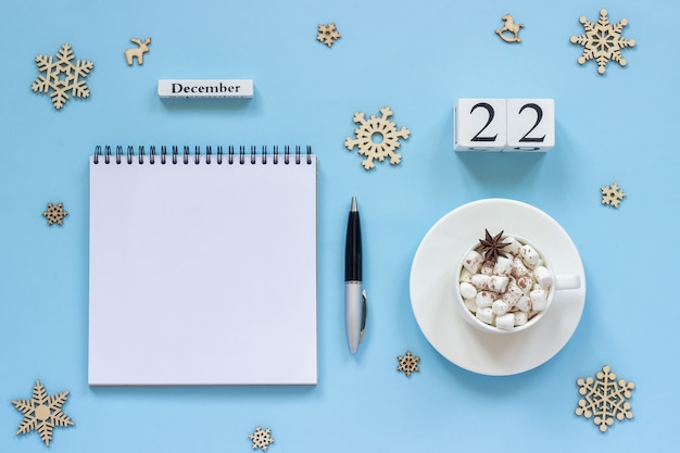 Winter composition. wooden calendar december 22 cup of cocoa with marshmallow and star anise, empty open notepad with pen and snowflake on blue background. top view flat lay mockup concept