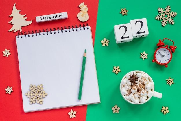 冬の構成。木製カレンダー12月22日マシュマロとココアのカップ、鉛筆、スノーフレーク、赤と緑の背景に目覚まし時計と空の開いたメモ帳。上面図フラットレイモックアップ