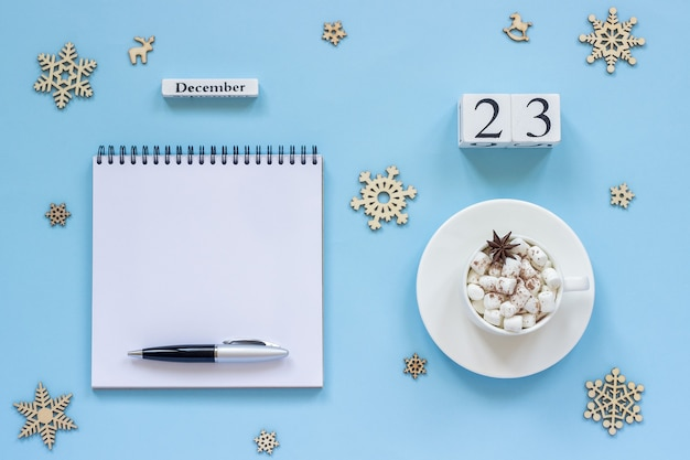 Зимняя композиция. деревянный календарь 23 декабря чашка какао с зефиром и звездчатым анисом, пустой открытый блокнот с ручкой и снежинка на синем фоне. вид сверху плоский макет концепции