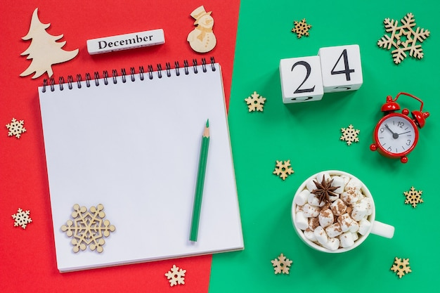 Зимняя композиция. деревянный календарь 24 декабря чашка какао с зефиром, пустой открытый блокнот с карандашом, снежинка, будильник на красном и зеленом фоне. вид сверху плоский макет