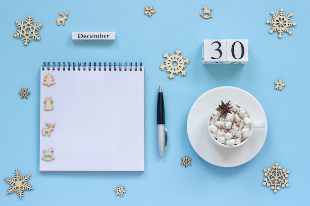 Winter composition. wooden calendar december 30 cup of cocoa with marshmallow and star anise, empty open notepad