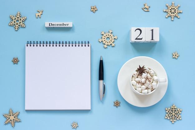 冬の構成。木製カレンダー12月マシュマロとスターアニスとココアのカップ、青い背景にペンとスノーフレークと空の開いたメモ帳。上面図フラットレイモックアップコンセプト