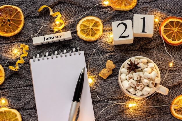 Зимняя композиция. деревянный календарь 21 января чашка какао с зефиром, пустой открытый блокнот с ручкой, сушеные апельсины, легкая гирлянда на сером вязаном фоне. вид сверху плоский макет