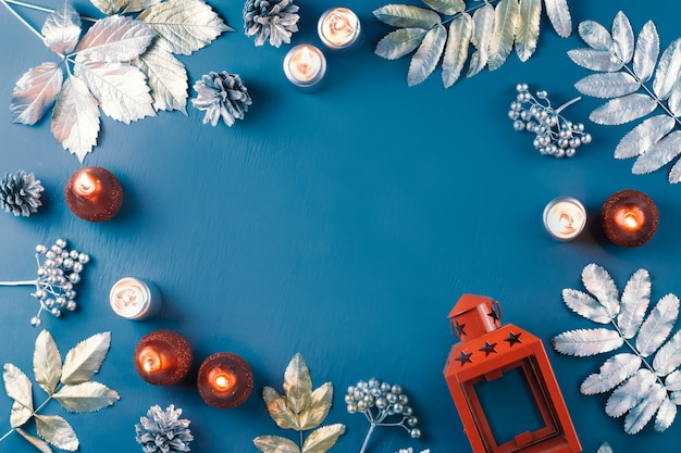 Winter concept flat lay with golden and silver leaves and red candles on blue