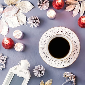 Winter concept flat lay with silver leaves, lantern, candles and hot coffee