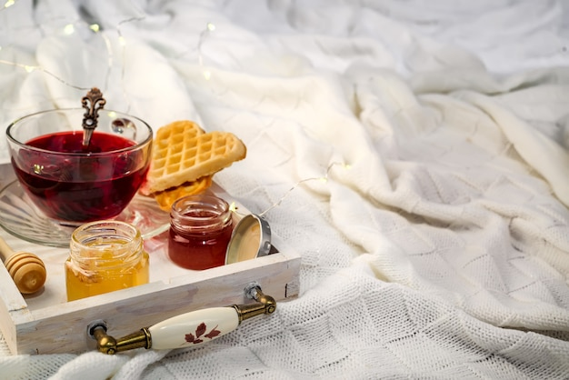 Winter concept with knitted blanket and hot tea with waffer, jam, honey on wooden tray