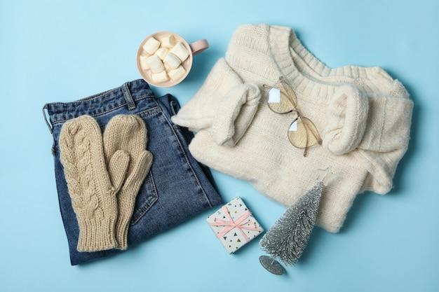 青の背景にセーターとギフトボックスと冬のコンセプト