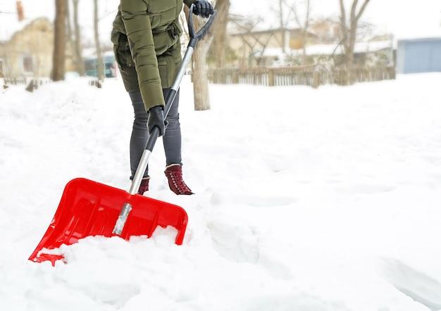 冬のコンセプト。赤いシャベルで除雪する女性
