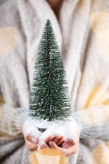 겨울 개념 젊은 손을 잡고 크리스마스 장식. 크리스마스 장식 아이디어. 여자, 골드 bokeh와 배경의 손에 크리스마스 장식.