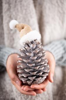 冬のコンセプト若い手がクリスマスの装飾を保持しています。クリスマスの装飾のアイデア。女性の手にクリスマスの装飾、金のボケ味の背景。