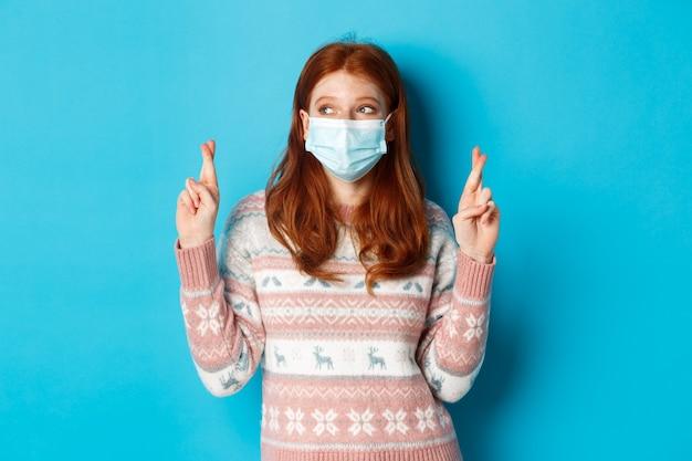 겨울, 코로나바이러스, 사회적 거리 개념. 빨간 머리에 얼굴 마스크를 쓰고 손가락을 꼬고 소원을 빌고 파란 배경 위에 서 있는 귀여운 희망적인 소녀.