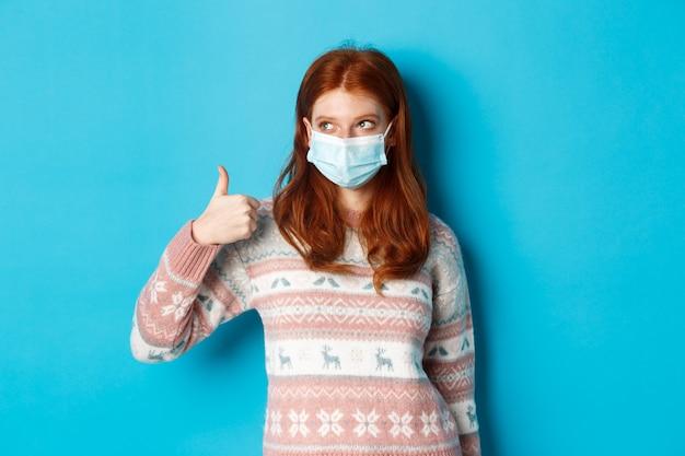 冬、コロナウイルスと社会的距離の概念。フェイスマスクとセーターを着たかわいい赤毛の女の子。左上隅のプロモーションを見て、親指を立てて、良い製品を賞賛しています。